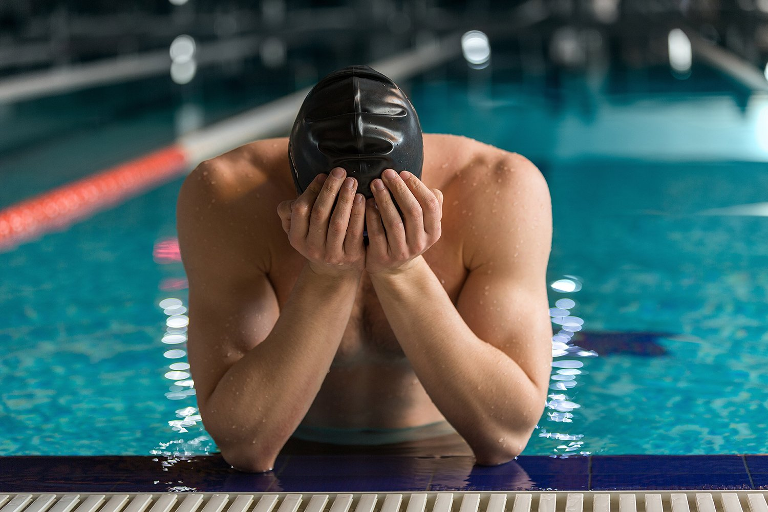 Male Swimmer with head in hands at the edge of the pool could use help from the winning edge to cope with a loss